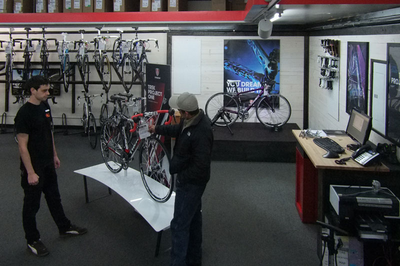 A customer looking at a Trek Madone 6.7 in front of our new Project One & Fit center